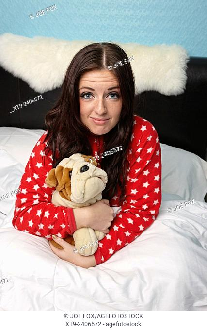early twenties woman holding cuddly dog soft toy in bed in a bedroom