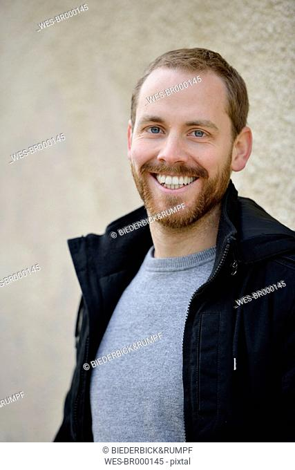 Portrait of laughing young man wearing black jacket