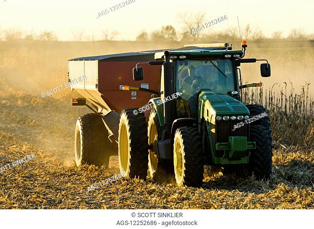 A farmer drives a tractor pulling a grain wagon full of harvested yellow grain corn during corn harvest in Southern Iowa; Iowa, United States of America