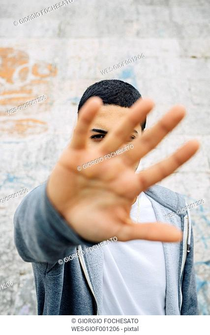 Young man raising his hand