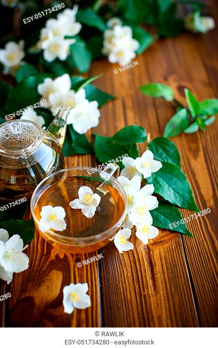 Jasmine tea in a glass pot on a wooden table