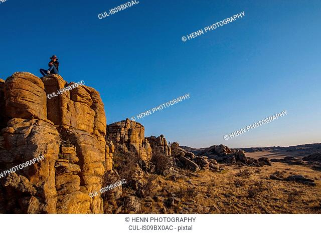 Woman on Baga Gazariin Chuluu rock cliff, Gobi desert, Mongolia