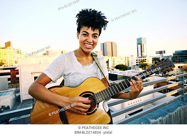 Smiling woman playing guitar on urban rooftop
