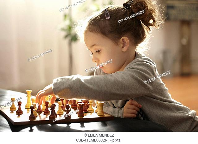 Girl playing chess indoors