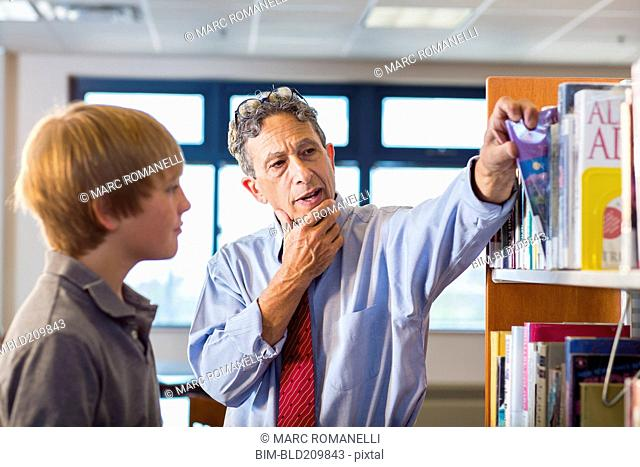 Teacher and student working in library