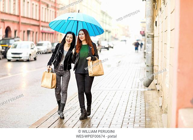 Two happy women shopping in the city on a rainy day