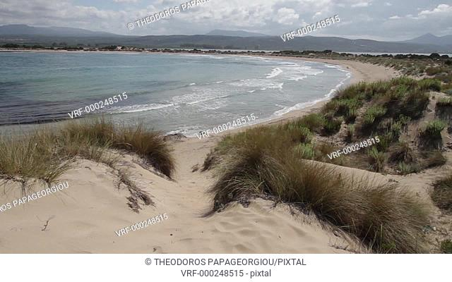 A woman walking on the sand dunes of Voidokilia beach. Messenia, Peloponnese, Greece