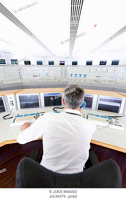 Engineer at computers in control room of nuclear power station