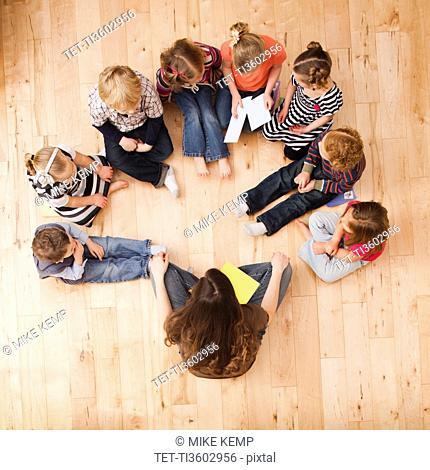 Children 2-3, 4-5 sitting in circle around teacher, directly above