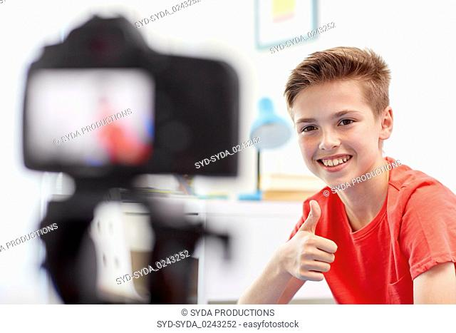 happy boy with camera recording video at home
