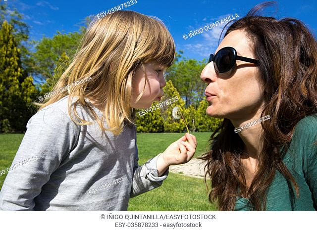 little child with grey shirt holding in her hand a dandelion plant and woman mother make a wish and blowing together, in green park