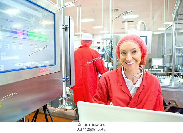Portrait smiling worker at control panel on production line food processing plant