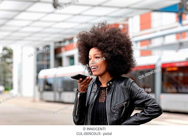 Young woman with afro hair at city train station, talking to smartphone