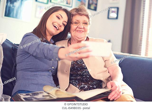 Young woman on sofa with grandmother taking smartphone selfie