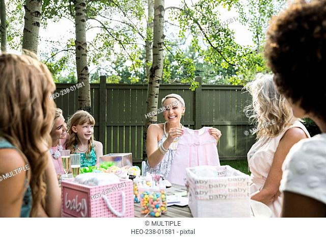 Pregnant woman opening gifts at backyard baby shower