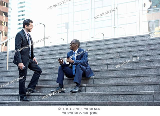 Two businessmen talking on stairs