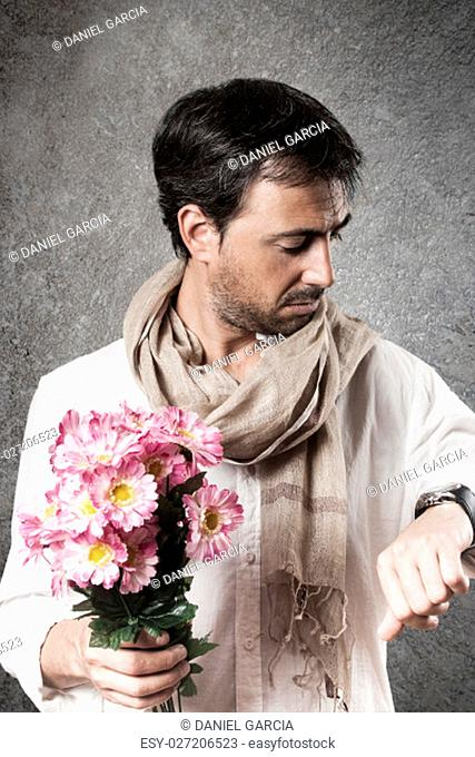 Man in love with a bouquet of flowers looking watch with concern. Vertical image