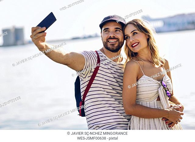 Spain, Andalusia, Malaga, happy tourist couple taking selfie with smartphone at the coast