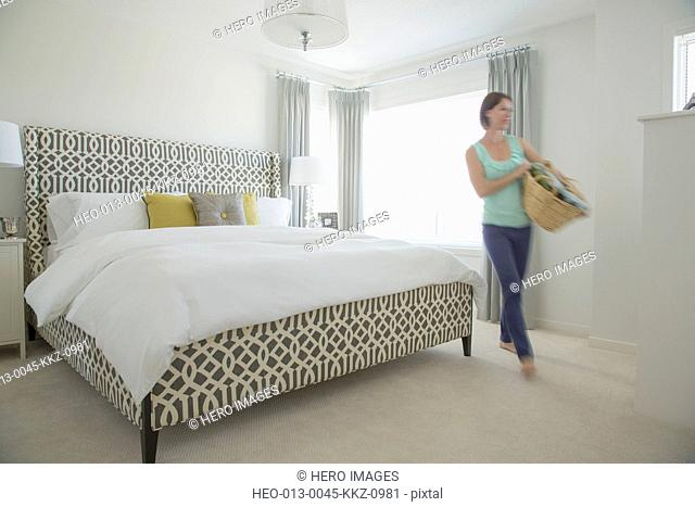 Mid-adult woman with laundry basket in modern bedroom