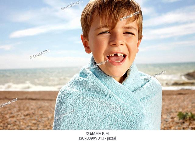 Boy at the beach, wrapped in a towel