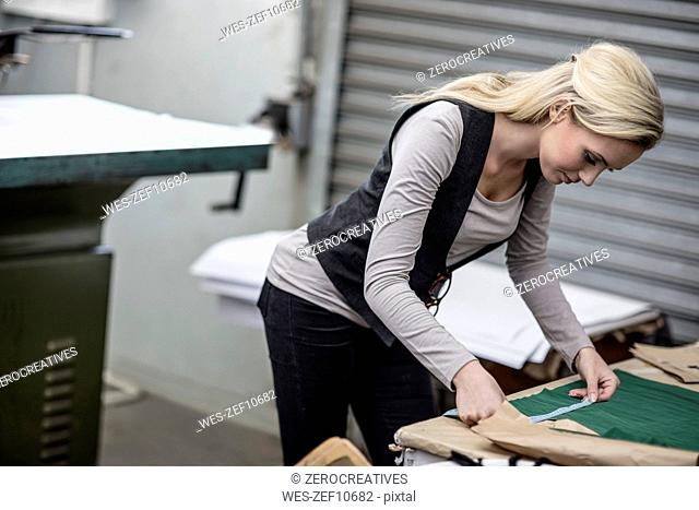 Young woman working with measuring tape in tailor shop
