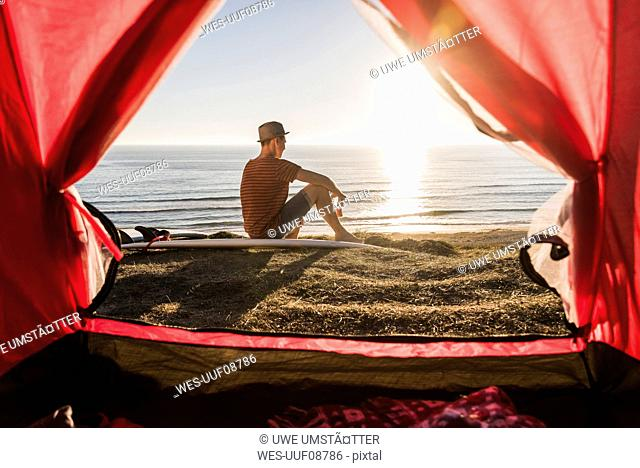 Young surfer camping at seaside
