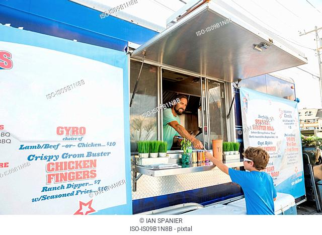 Man in fast food trailer serving young boy through hatch
