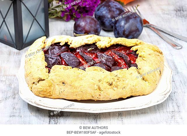 Plum galette on wooden table. Raw plums and pumpkins in the background. Autumn party setting