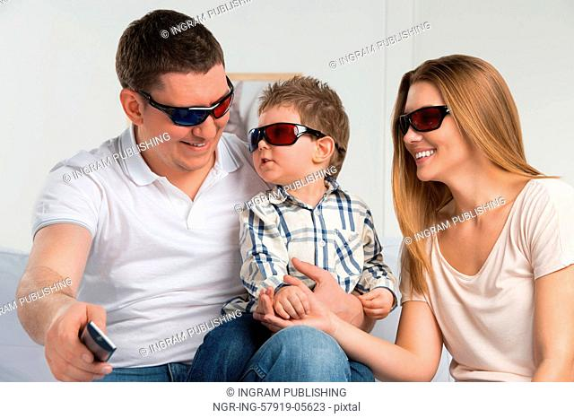 Family laughing while watching television together in the living-room wearing 3d glasses