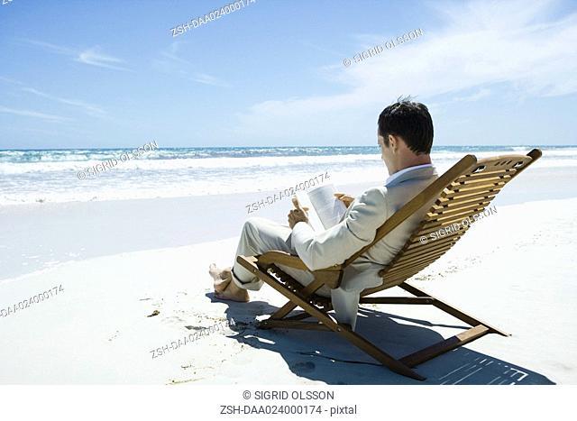 Businessman sitting in deckchair on beach, reading book