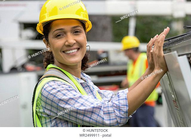 Portrait of happy Hispanic female utility worker smiling at site