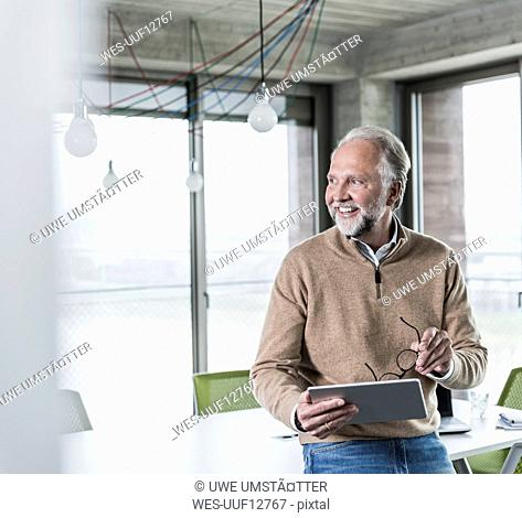Smiling casual mature businessman holding tablet in conference room in office