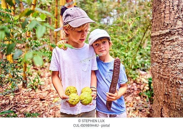 Boys in jungle holding coconuts and seed, Aguas Calientes, Chuquisaca, Bolivia, South America