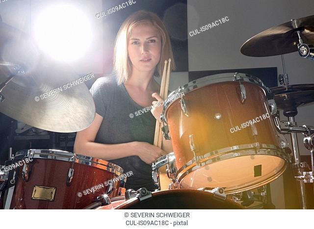Female drummer sitting behind drums