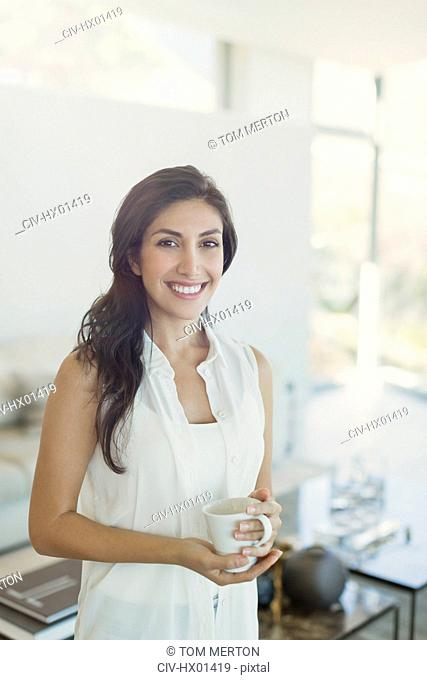 Portrait smiling brunette woman drinking coffee in living room