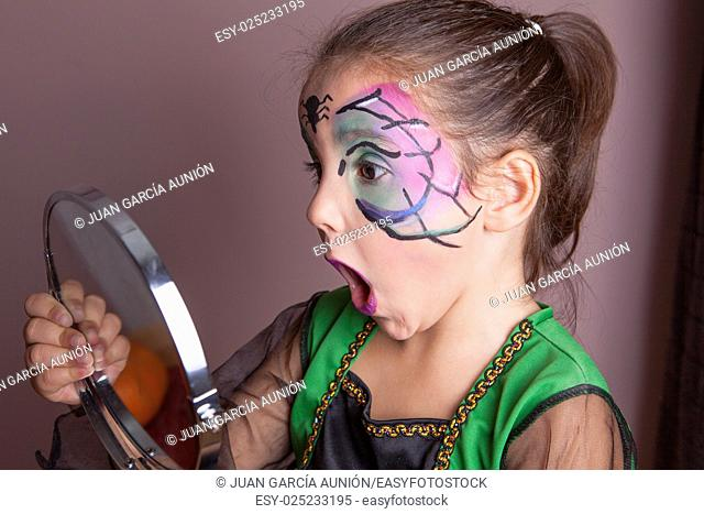 Little girl looking surprised into the mirror after face painting session before halloween party