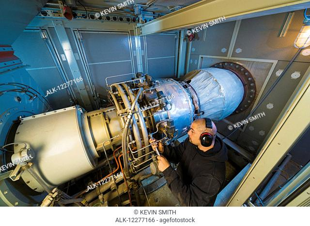 Worker working on an electrical power plant, gas turbine generator and drive shaft, Prudhoe Bay, Arctic Alaska, USA, Summer