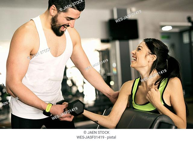 Man training woman lifting weights in gym