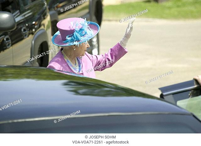 Her Majesty Queen Elizabeth II in bright purple outfit and hat, waving to the crowd as she enters Presidential Limousine in Williamsburg Virginia