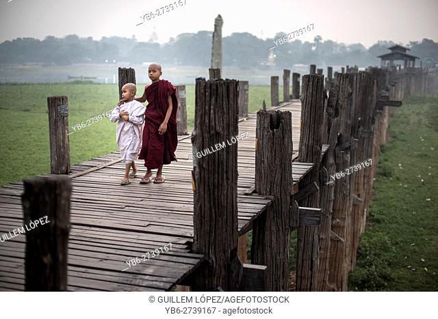 Two young novice Buddhist monks walking on the U Bein Bridge in Amarapura, Myanmar