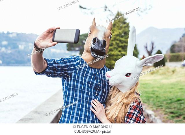 Couple wearing horse and rabbit masks taking smartphone selfie, Lake Como, Italy