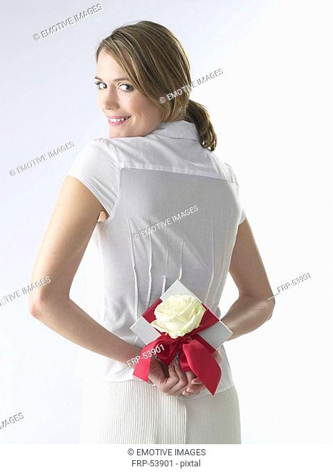 Woman with a gift and white rose blossom