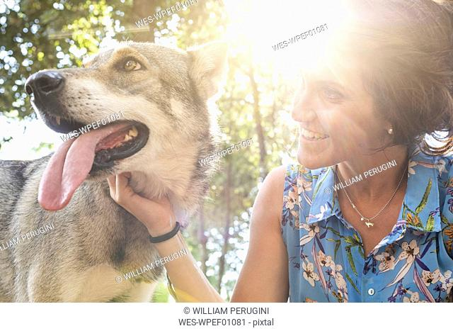 Smiling young woman stroking her dog at backlight