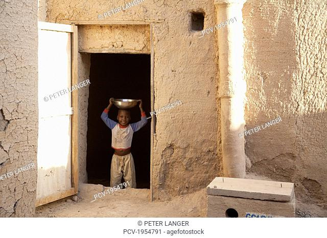 Boy standing with a container on head at door in Djenne, Mali