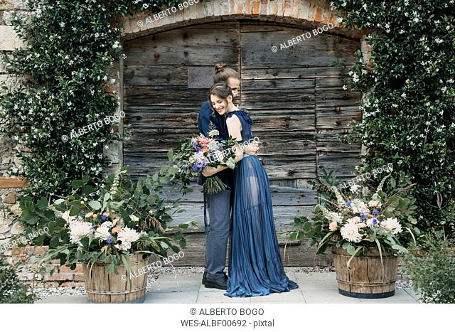 Bride and groom standing at a wooden gate embracing