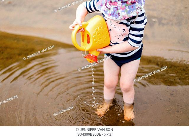 Girl standing ankle deep in lake pouring water from toy watering can, Huntsville, Canada