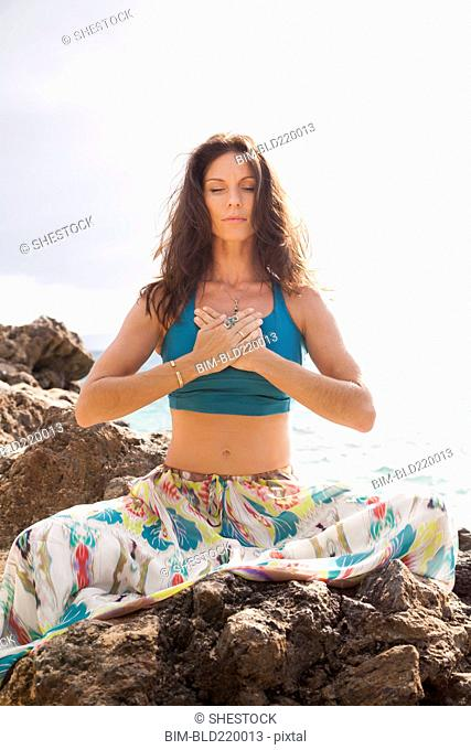 Close up of woman meditating on rocky beach