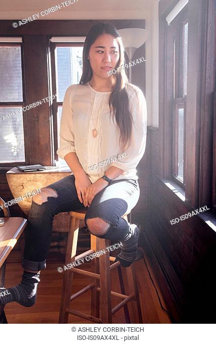 Woman wearing torn skinny jeans sitting on stool looking away