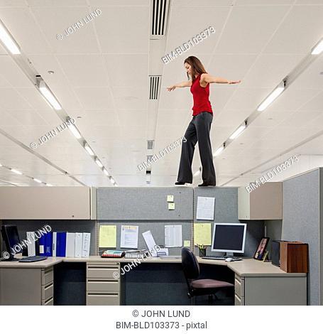 Mixed race businesswoman walking along cubicle wall