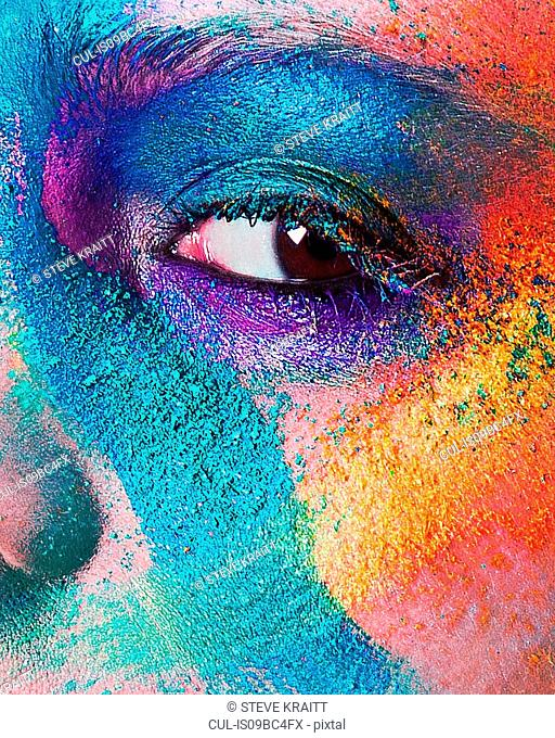 Studio portrait of young woman's face with multi coloured powder eye shadow, close up